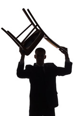 silhouette of man with chair over his head