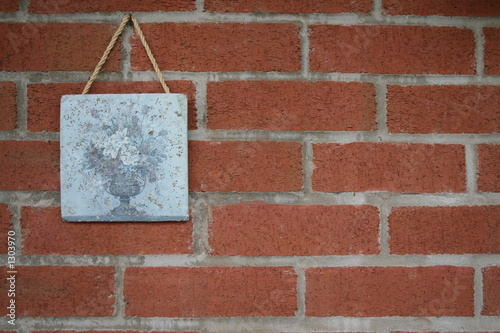 art tile on a red brick wall