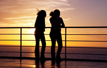 two girls black silhouette and red sunset