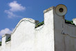 white stucco building with green tile roof