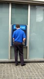 a man using the cash/bank machine poster