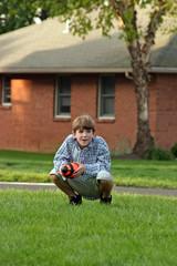boy squatting with football