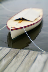 small sailboat tied to pier