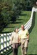 couple walking a white fence in the country