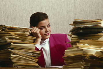 woman in office overwhelmed by paperwork