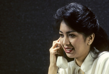 asian woman in office on phone