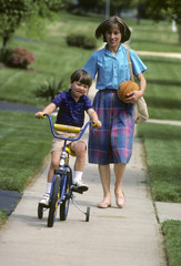 mother helps son learn to ride a bike