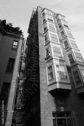 tall building with fire escape and bay windows