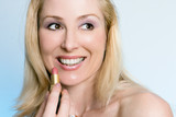 beauty - happy female applying pink lipstick poster