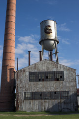 abandoned factory building with water tower and ch