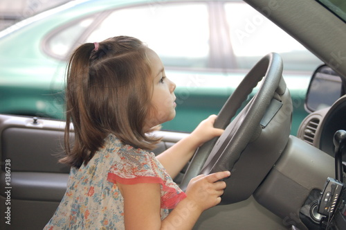 little girl driving a car