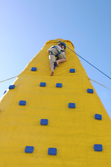 child coming down from a climbing wall