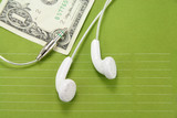 white headphones with dollar poster