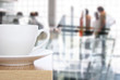 Leinwanddruck Bild - coffee cup on table in front of office