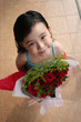 girl standing & holding bouquet of roses