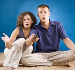 young shocked couple on carpet with remote control