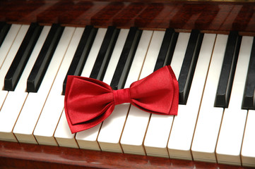 red bow-tie on piano keys