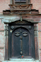 nepalese carved wooden doorway with buddha's eyes