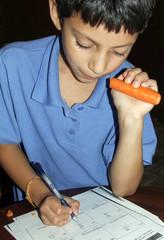 boy doing homework eating a carrot