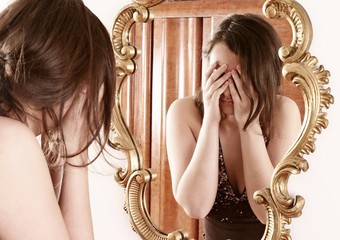 sad woman  in front of  a mirror