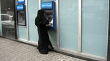 muslim woman wearing veil using the cash machine poster