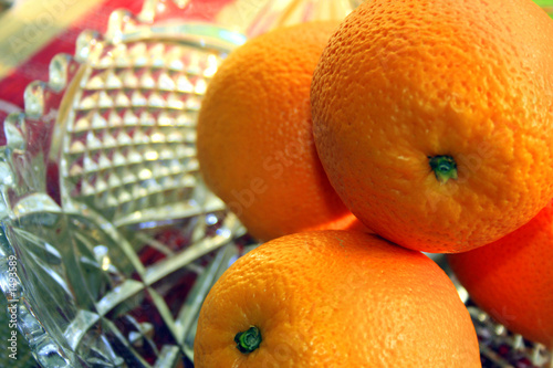 4 oranges in a glass fruit bowl