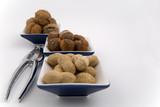 walnuts, hazelnuts and peanuts in three bowls poster