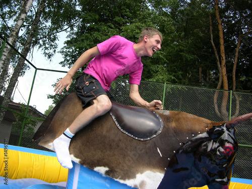 Leinwandbild Motiv boy on bull simulator