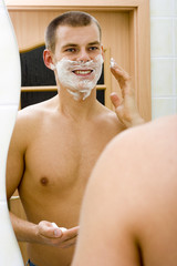 young man in the bathroom's mirror with shave foam on face