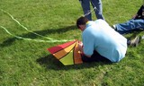 a man sitting on the grass fixing a kite poster