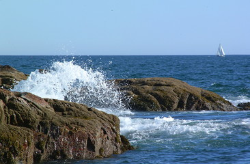 waves crashing on pink granite boulders