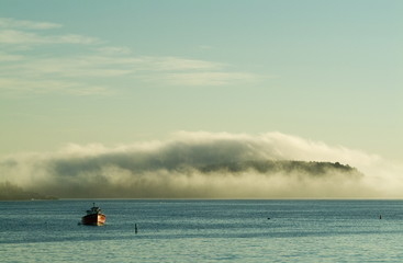 island covered by fog and lobster boat