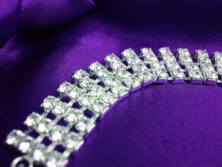 close up of dimond necklace on a violet background