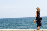 woman staying on wall, watching at the sea poster