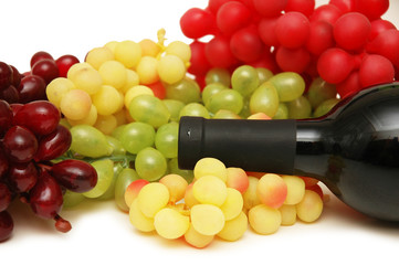 grapes and bottle of wine isolated on white