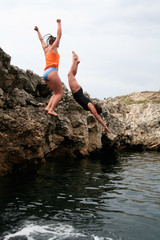 girls jumping off rocks into water