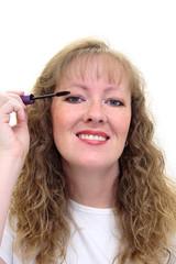 woman putting on eye makeup