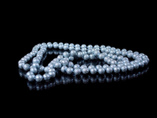 string of blue pearls isolated on black with reflection
