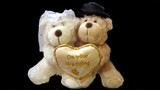 toy of bride and bridegroom carrying one heart poster
