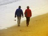 seniors strolling on beach poster