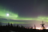full moon and active colorful aurora over fairbank