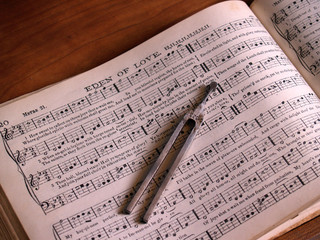 shaped note hymnal with song leader's tuning fork