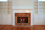 lit fireplace with built in bookshelves poster