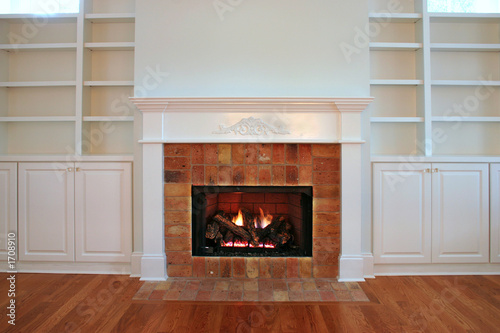lit fireplace with built in bookshelves
