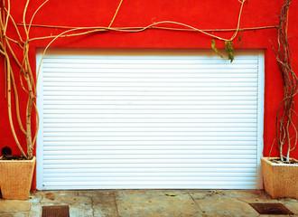 bright orange wall with a white garage door
