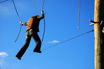 courageous woman standing on a steel wire