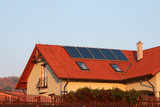 house with solar panels on the roof for water heating poster
