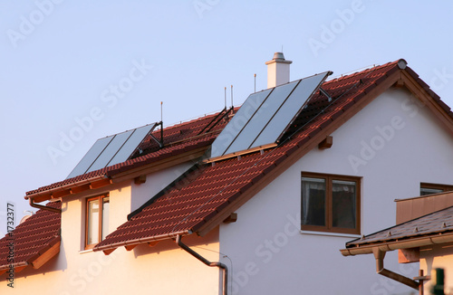 house with solar panels on the roof for water heating