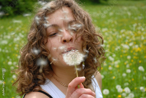 girl is blowing on dandelion
