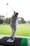 woman at driving range poster